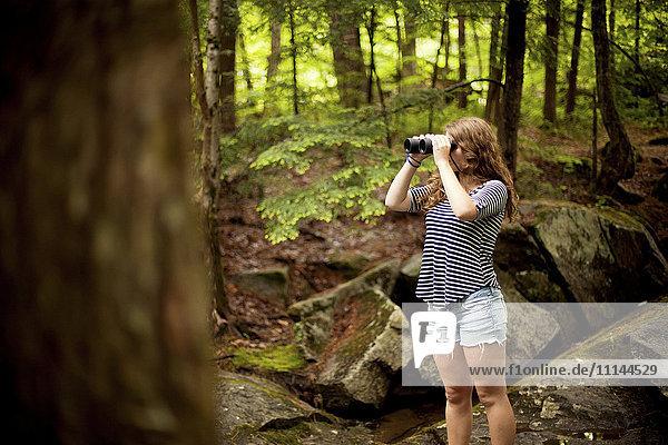 Girl looking through binoculars in forest