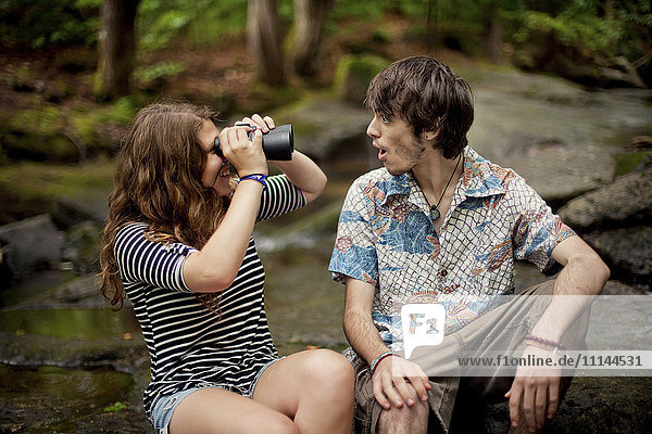 Couple using binoculars on boulders in forest