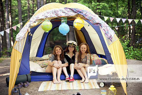 Girls relaxing in camping tent