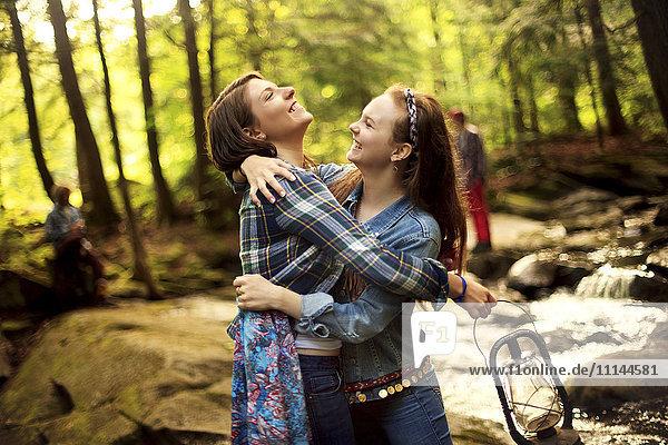 Girls hugging in forest creek