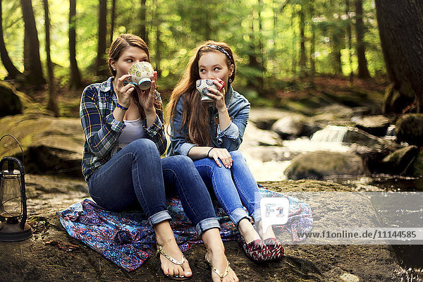 Girls drinking coffee on forest rock