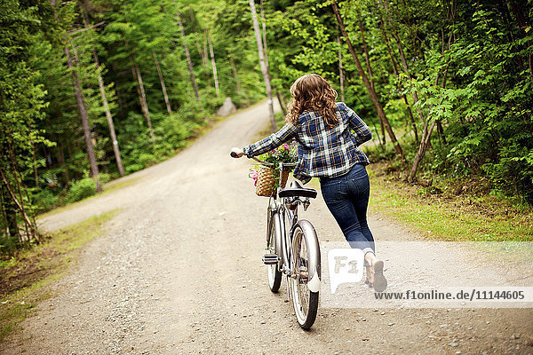 Rear view of girl pushing bicycle on dirt path