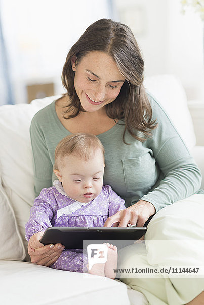 Caucasian mother reading to baby with Down Syndrome