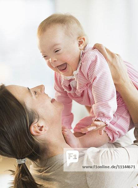 Caucasian mother playing with baby girl with Down Syndrome