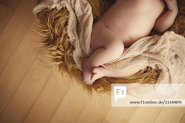 Close up of baby girl laying on furry carpet