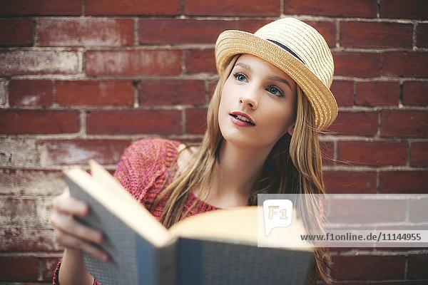 Girl reading book near brick wall