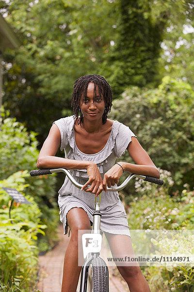 African American woman sitting on bicycle in backyard