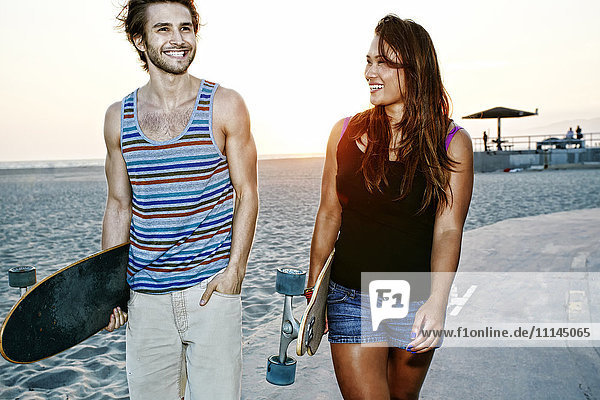 Couple carrying skateboards on beach