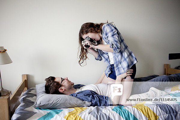 Woman photographing boyfriend on bed