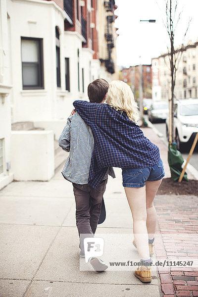 Caucasian couple walking on city sidewalk