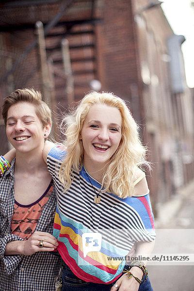 Caucasian couple laughing on city sidewalk