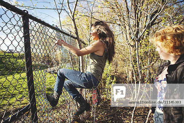 Women climbing through hole in chain-link fence