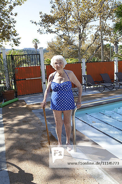 Older Caucasian woman standing with cane near swimming pool