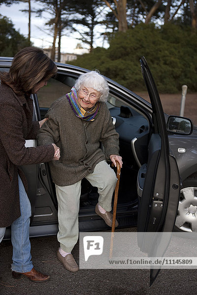 Woman helping mother out of car