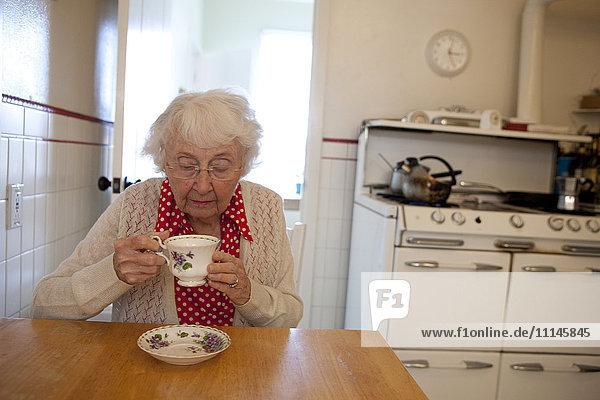 Older woman drinking tea in kitchen