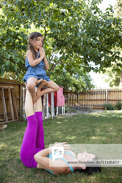 Mother practicing yoga with daughter in backyard