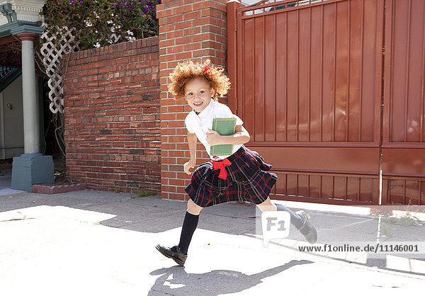 Smiling girl in school uniform running in driveway Smiling girl in school uniform running in driveway