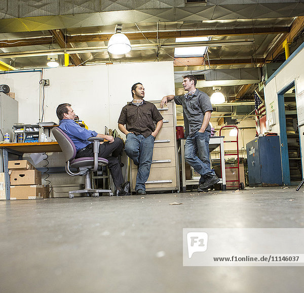 Manager and workers talking in warehouse