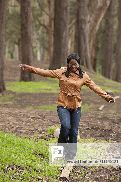 Black woman balancing on log in forest