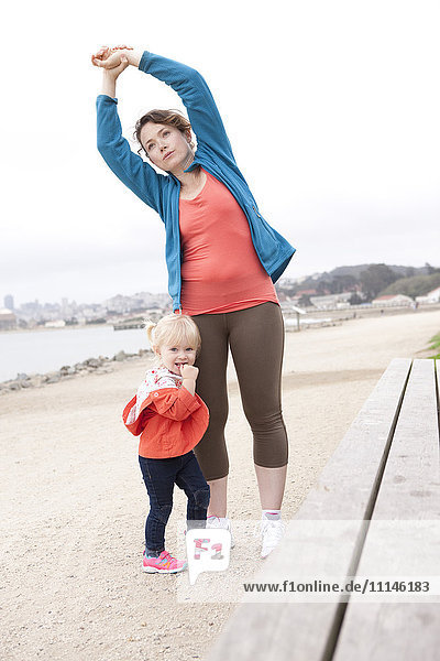 Caucasian mother and daughter stretching on beach
