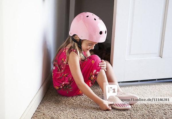 Caucasian girl wearing bike helmet in doorway