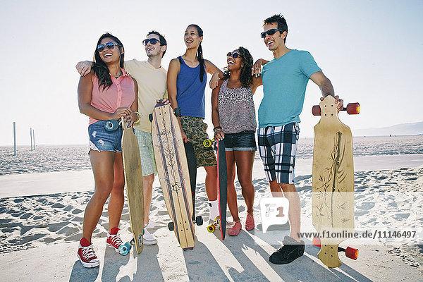 Friends holding longboards on beach