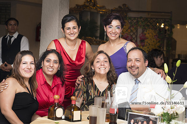 Hispanic family smiling at wedding reception