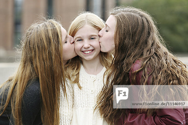 Close up of smiling sisters kissing outdoors