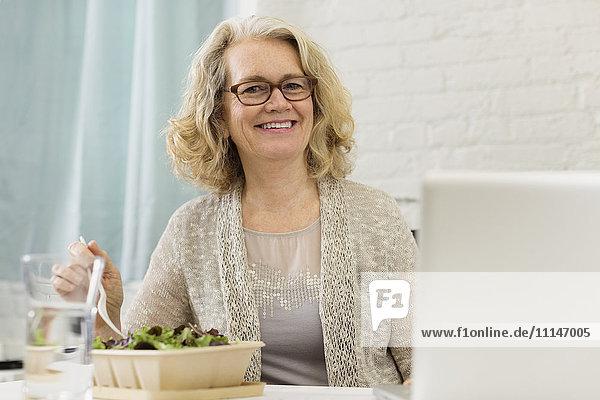 Senior Caucasian businesswoman eating salad