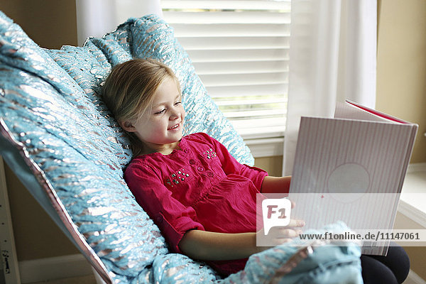 Smiling girl reading book in armchair