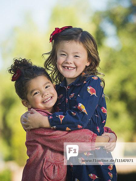 Mixed race girls hugging outdoors