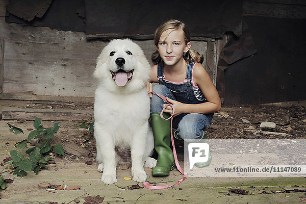 Girl crouching with dog in dilapidated shed