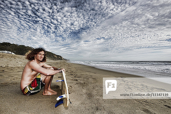 Caucasian man holding surfboard on beach