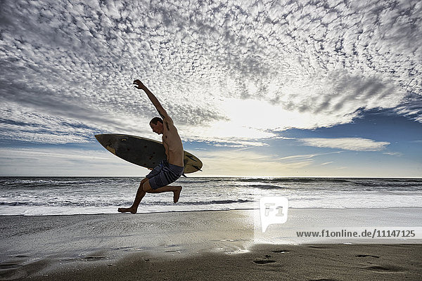 Caucasian man jumping with surfboard on beach