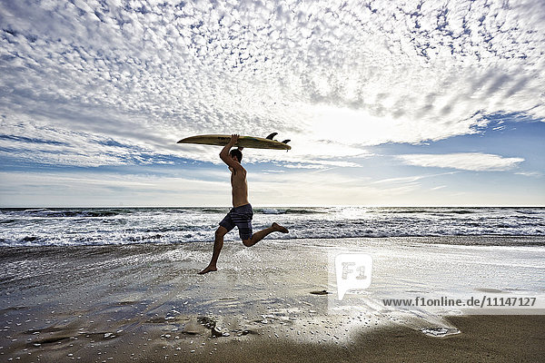Caucasian man jumping with surfboard on beach Caucasian man jumping with surfboard on beach