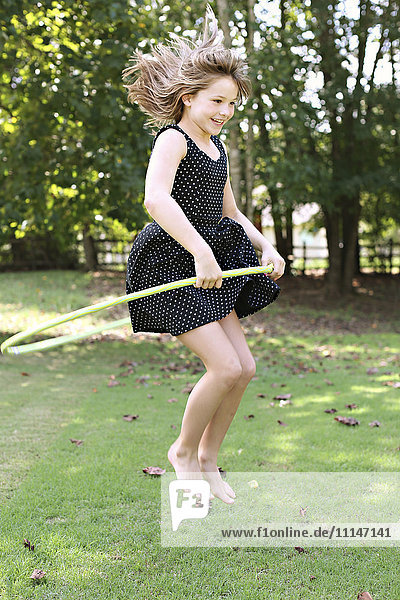 Smiling girl playing with plastic hoop in field