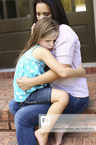 Close up of mother comforting daughter on front stoop
