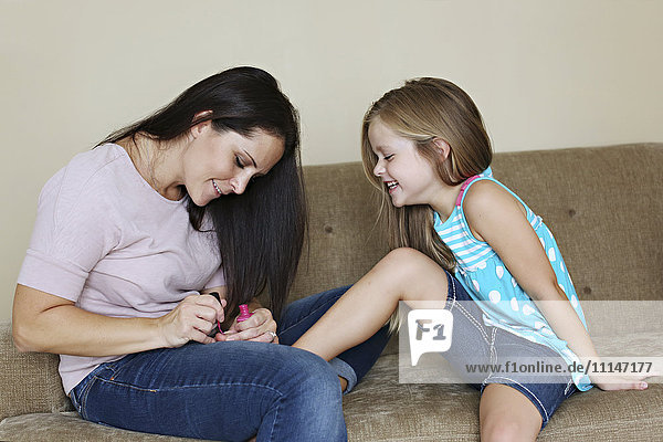 Mother painting toenails of daughter on sofa