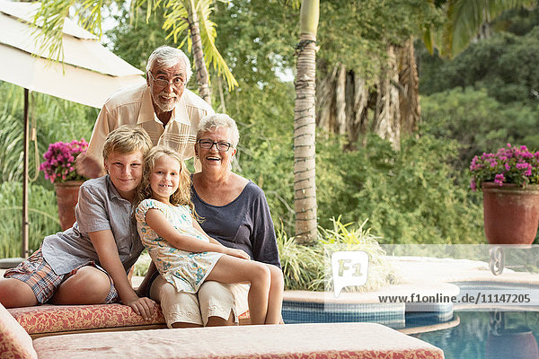 Older Caucasian couple and grandchildren smiling outdoors