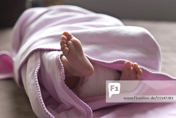 Close up of feet of baby girl in blanket