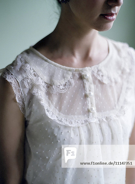 Close up of woman wearing lace blouse