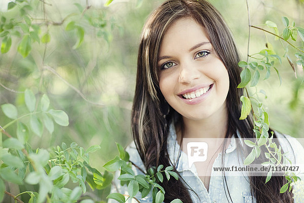 Close up of smiling woman standing in garden