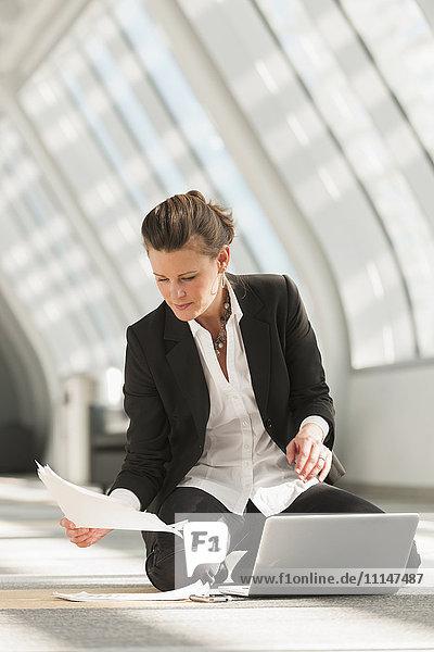Caucasian businesswoman using laptop on lobby floor