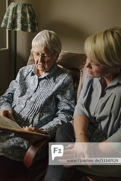 Older woman reading to granddaughter in living room