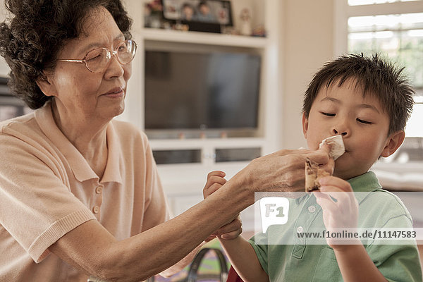 Asian grandmother wiping face of grandson at table