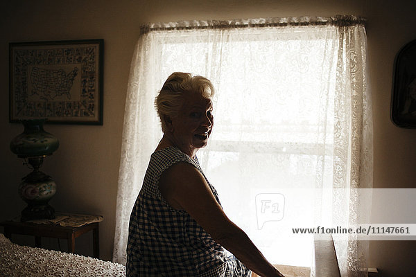 Smiling older woman sitting on bed