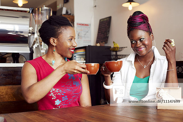 Women toasting each other with coffee in cafe