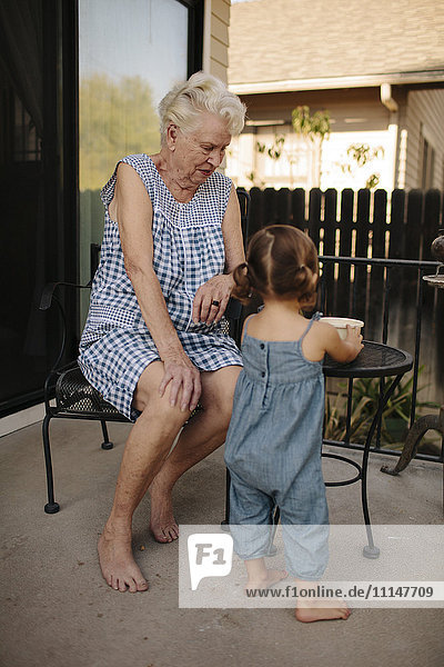 Grandmother and granddaughter playing on patio