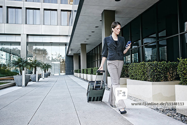 Caucasian businesswoman rolling baggage outdoors