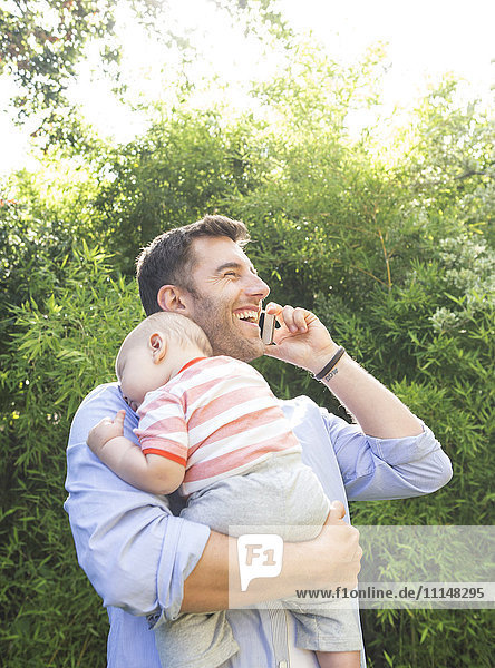 Caucasian father on cell phone holding baby